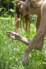 Young woman bending over to smell wildflowers