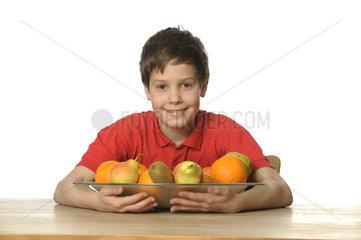 Junge haelt Obstschale