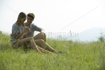 Couple sitting on meadow  woman picking flower petals