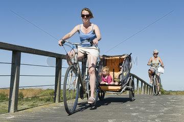 Multi-generation family enjoying bicycle ride  children sitting in bicycle trailer