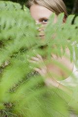 Woman peeking through fern frond  portrait
