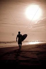 Surfer laeuft am Strand