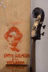 Kopf eines Kontrabass der vor einem Graffiti an der Wand lehnt