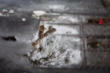 Baukran spiegelt sich in einer Wasserpfuetze