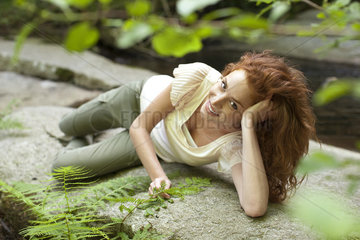 Young woman relaxing on rock