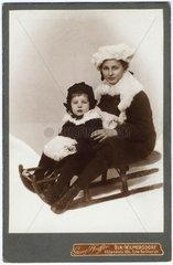 Mutter und Kind fahren Schlitten  um 1910