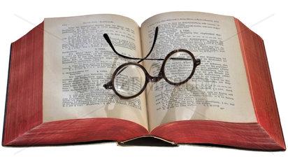Brille auf aufgeschlagenem Buch  1900