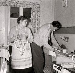 Hausfrau  Ehemann  hilft beim Abwasch in der Kueche  1957