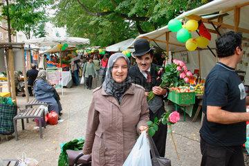 Charlie Chaplin verschenkt eine Rose an eine Tuerkische Frau in Kreuzberg