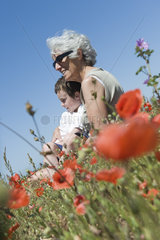 Grandmother and young grandson sitting together in field of poppies