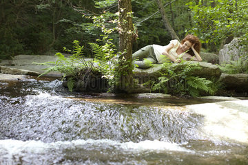 Young woman relaxing on rock by flowing stream