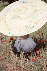 Little girl with parasol in meadow  mid section