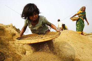 A girl sifting sand