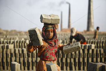 Girl child worker carrying bricks