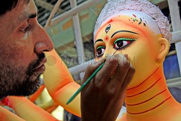 Artisan works on the clay idol
