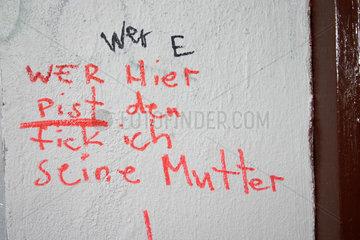 androhung Graffiti am Eingang ein Wohnhaus in Kreuzberg.