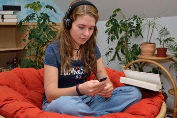 Jugendliche sitzt mit MP3-Player gemuetlich in Couchsessel