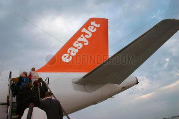 Passagiere steigen in eine easyJet Flugzeug.