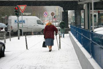 eine Alte Frau mit Stock lauft langsam auf die Strasse