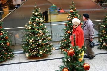 Paar zwischen die Weihnachtsbaeume beim shoppen