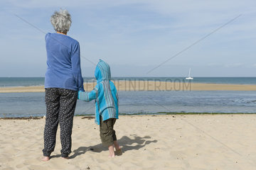 Grandmother and grandson standing together on beach  looking at boat on horizon