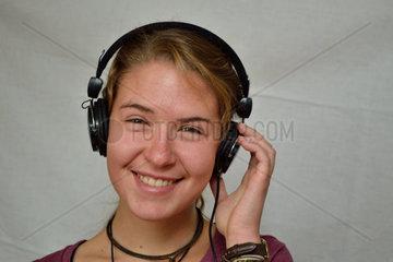 Jugendliche hoert mit Kopfhoerer begeistert Musik