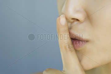 Young woman with finger held to lips  cropped