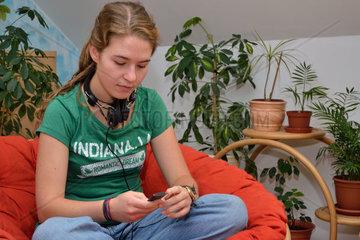 Jugendliche mit Kopfhoerer sucht am MP3-Player nach Musik