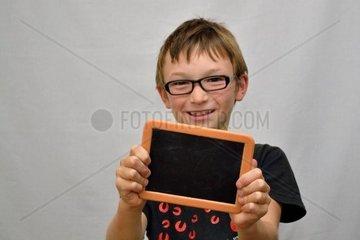 Junge haelt kleine Tafel in der Hand und lacht