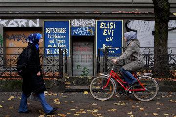 Eine junge Frau laeuft an einem Laden entlang der Deutschkurse fuer tuerkische Frauen und Maedchen anbietet