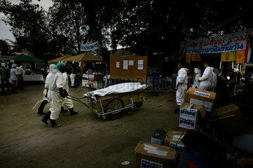 Helfer bringen eine Leiche zur DNA-Untersuchung in den Tempel.