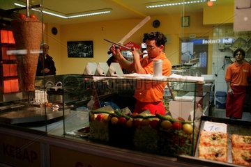 Ein Verkaeufer in einem Doenerladen schaerft sein Messer