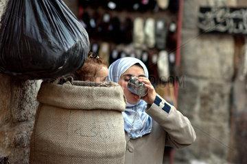 Eine unbekannte junge Frau trinkt an einer oeffentlichen Wasserstelle