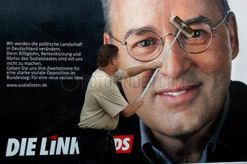 Ein Helfer klebt Wahlplakate der PDS