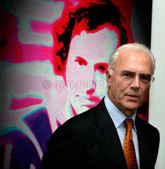 Franz Beckenbauer vor einem Portrait von sich in der Ausstellung Rundlederwelten