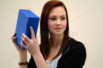 Teenager schuettelt verschlossene blaue Kartonbox
