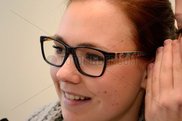 Person fluestert Teenager etwas ins Ohr