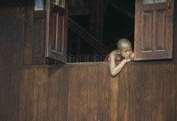 Novizen schauen aus einem Holzfenster