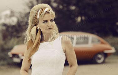 Frau im Sommerkleid vor einem Jaguar E