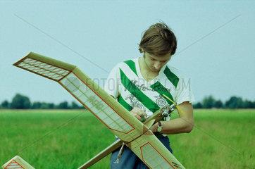 Junger Mann mit Modellflugzeug