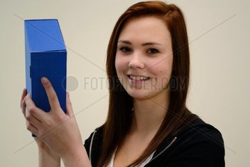 Teenager schuettelt erfreut blaue Geschenkschachtel