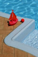 Spielsegelboot an einem Pool