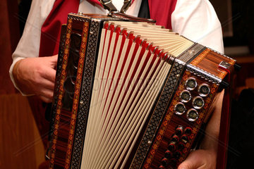 Man in costume plays on a Styrian harmonica