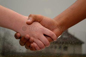 Handschlag zweier Teenager unterschiedlicher Hautfarbe