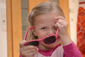 kleines Maedchen in rosa Kleidung mit Sonnenbrille