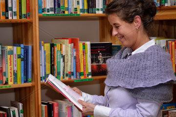 Frau schmunzelt beim Lesen in Buecherei