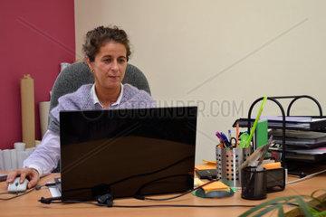Geschaeftsfrau arbeitet im Firmenbuero am Computer