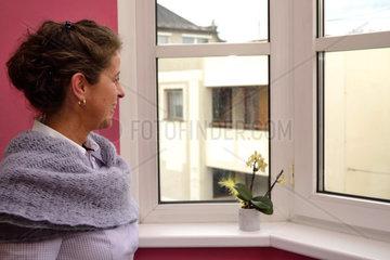 Frau schaut zufrieden aus Fenster und laechelt