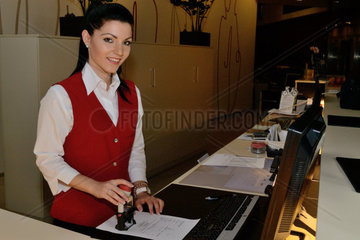 Rezeptionistin bestaetigt Rechnung mit Firmenstempel