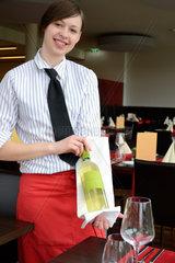 Kellnerin praesentiert liebevoll die Weinflasche